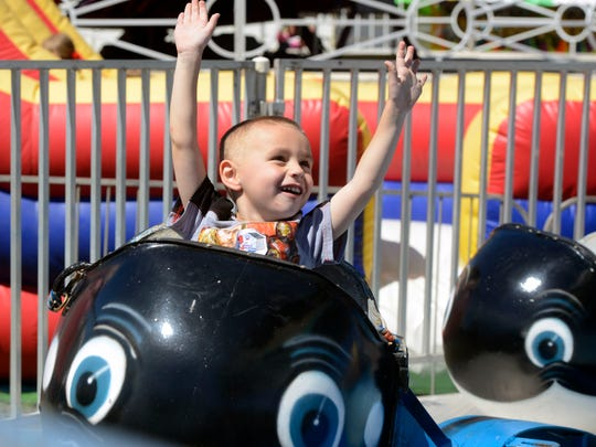 Aiden Knight, 3, enjoys a carnival ride at last year's Santa Rosa County Fair. The fair returns Friday.