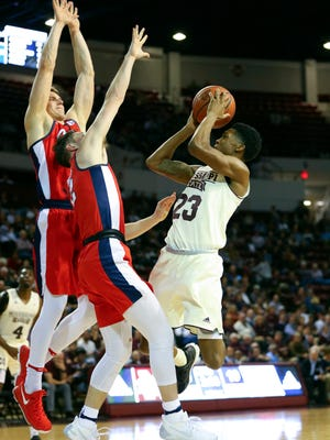 MSU's Tyson Carter (23) shoots the ball against Mississippi Rebels guard Cullen Neal (2) and forward Justas Furmanavicius (50).