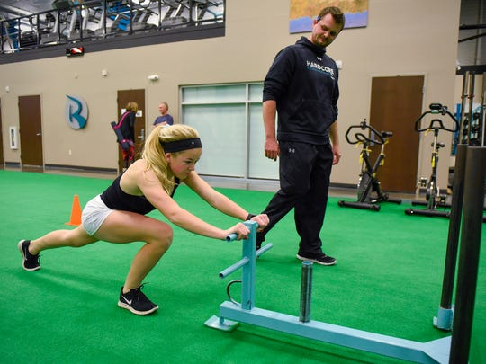 Trainer Isaiah McBride, director of Hardcore Elite Sports Performance at Rejuv, watches as Sofie Streich, 15, pushes a sled during her workout Wednesday, Nov. 15, at Rejuv in Waite Park.