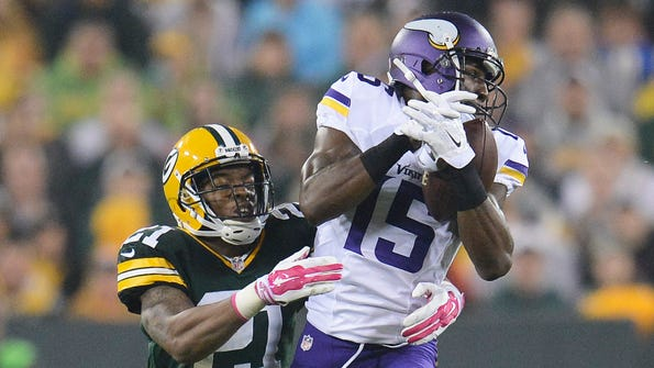 Green Bay Packers safety Ha-Ha Clinton-Dix (21) gives up a catch to receiver Greg Jennings (15) against the Minnesota Vikings during Thursday night's game at Lambeau Field.