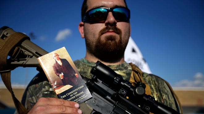 Brian Chrusciel of Fort Worth poses for a portrait holding a pocket version of the U.S. Constitution and his Bushmaster AR-15 rifle, as he and members of the Open Carry Tarrant County group gathered for a demonstration May 29, 2014, in Haltom City, Texas.