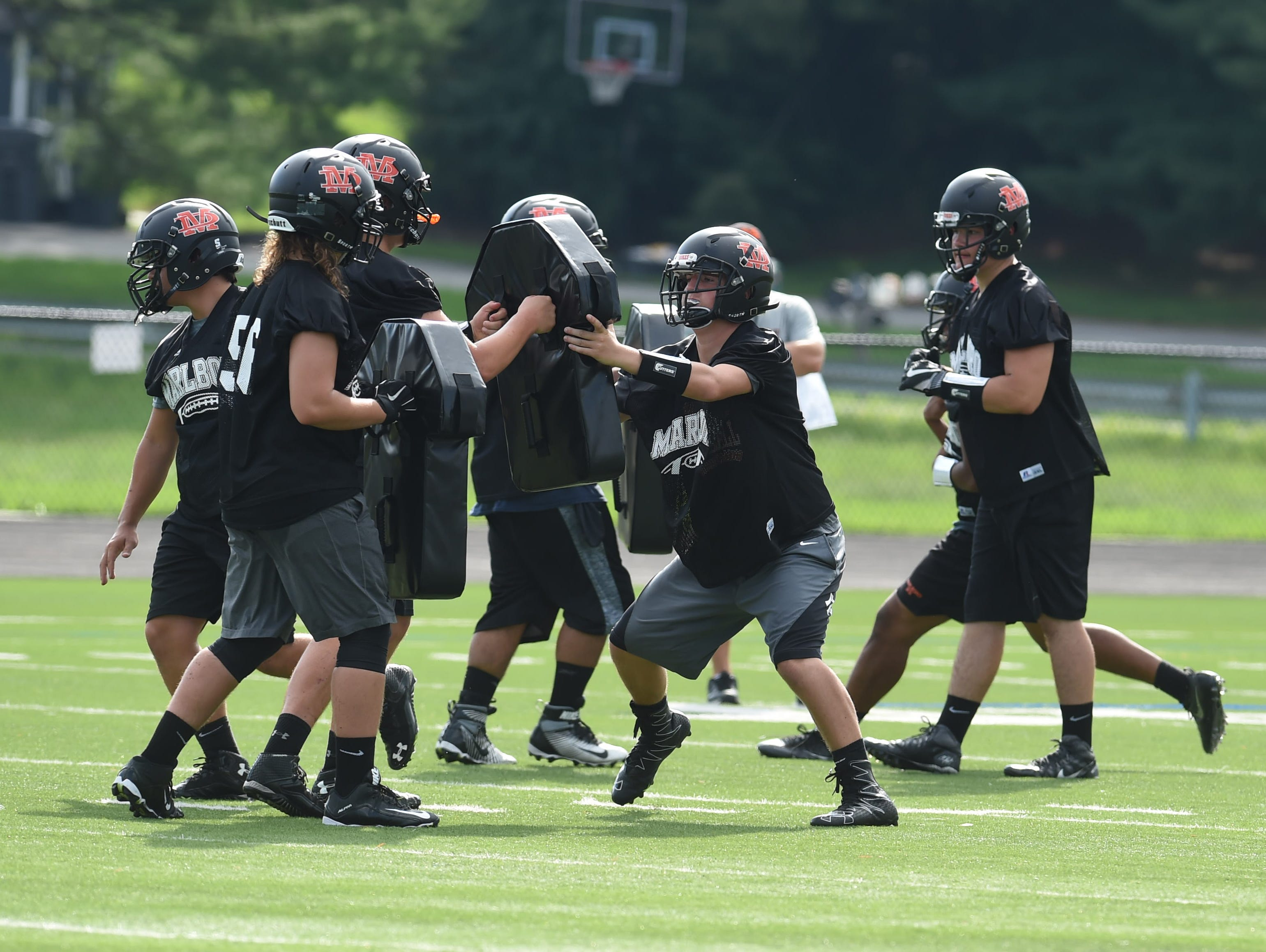 Sophomore Nick Esposito, left, prepares for a block during football preseason practice at Marlboro High School.