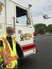 Junior Police Academy member Nate Schneider uses a Oakfield fire truck to shield the wind created from a landing Flight for Life helicopter. The helicopter made a stop Thursday, June 25, at the Oakfield High School as part of the three-week Junior Police Academy class.