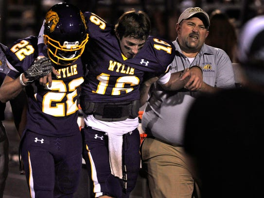 Wylie High School quarterback Sam King is helped along