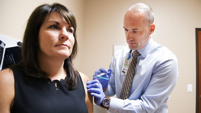Dr. Devin Minior administers a flu shot to Karen Salas, director of medical staff services for Banner Urgent Care, on Sept. 20, 2017. Flu shots are required for all Banner employees.