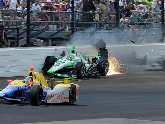 IndyCar driver Sage Karam (24) hits the wall coming out of turn one during the 100th running of the Indianapolis 500 Sunday, May 29, 2016, afternoon at the Indianapolis Motor Speedway.