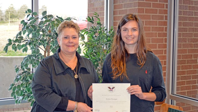 Mountain Home High School senior Jessica Swonger, daughter of Darin and Melissa Swonger, accepts the President's Volunteer Service Award from Assistant Principal Lindsey Blevins on Friday, March 18 in the high school library.