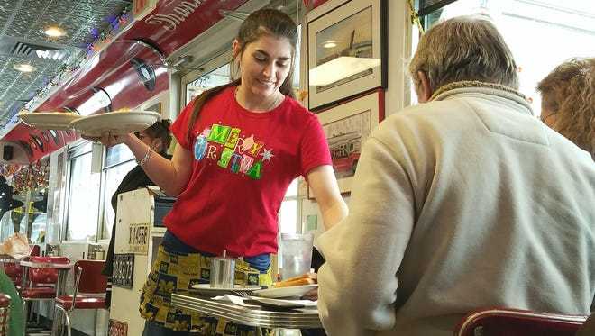 Waitress Kait Kirkendall delivers plates of food to customers at Powers Diner on Monday, Dec. 25, 2017. The diner's employees volunteered to work Christmas day, when it's not usually open.