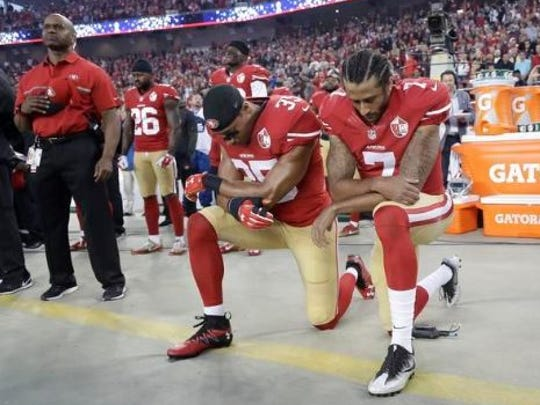 San Francisco 49ers safety Eric Reid (35) and quarterback Colin Kaepernick (7) kneel during the national anthem before an NFL football game against the Los Angeles Rams in Santa Clara, Calif., Monday.