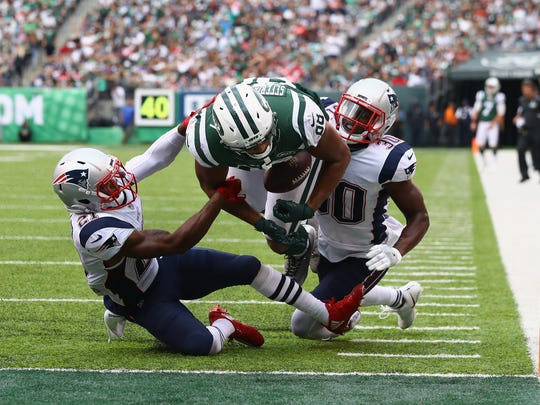 EAST RUTHERFORD, NJ - OCTOBER 15:  Tight end Austin Seferian-Jenkins #88 of the New York Jets is seen fumbling the ball after what was originally called a touchdown against strong safety Duron Harmon #30 and cornerback Malcolm Butler #21 of the New England Patriots during the fourth quarter of their game at MetLife Stadium on October 15, 2017 in East Rutherford, New Jersey. The Replay Official reviewed the runner broke the plane ruling, and the play was reversed and called a fumble.  (Photo by Al Bello/Getty Images) *** BESTPIX *** ORG XMIT: 700070680 ORIG FILE ID: 861700940