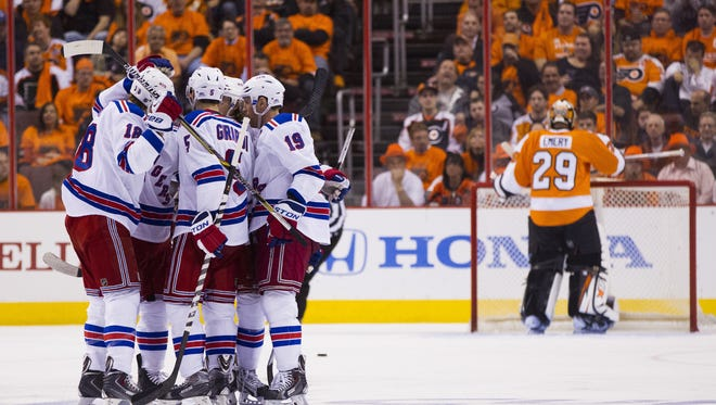 The Rangers' Dan Girardi, center left, celebrates his goal against the Philadelphia Flyers' Ray Emery, right, during the second period of Game 3  Tuesday night.