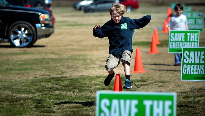March 5, 2016 - Matthew Montgomery, 8, leaps parking cones as a group of protesters gather on the Greensward Saturday in opposition of a City Council decision this week to turn the Greensward over to the Memphis Zoo for parking. Overflow parking took over a quarter of the Greensward, a typical turn out for a warm Saturday.(Jim Weber/The Commercial Appeal)