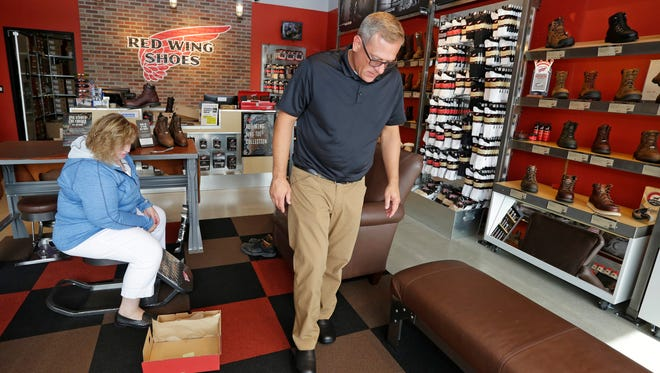 Tom Vipond of Algona, Iowa, tries a pair of shoes at the Red Wing Shoe store, Wednesday, August 9, in Sheboygan.  At left is co-owner/store manager Kelly Church observing the fitting.