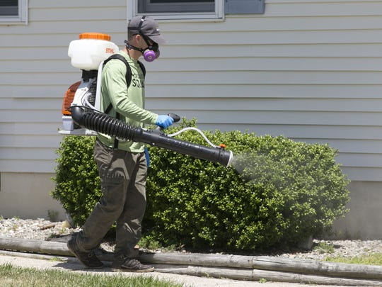 A pest control worker sprays insecticide outside a