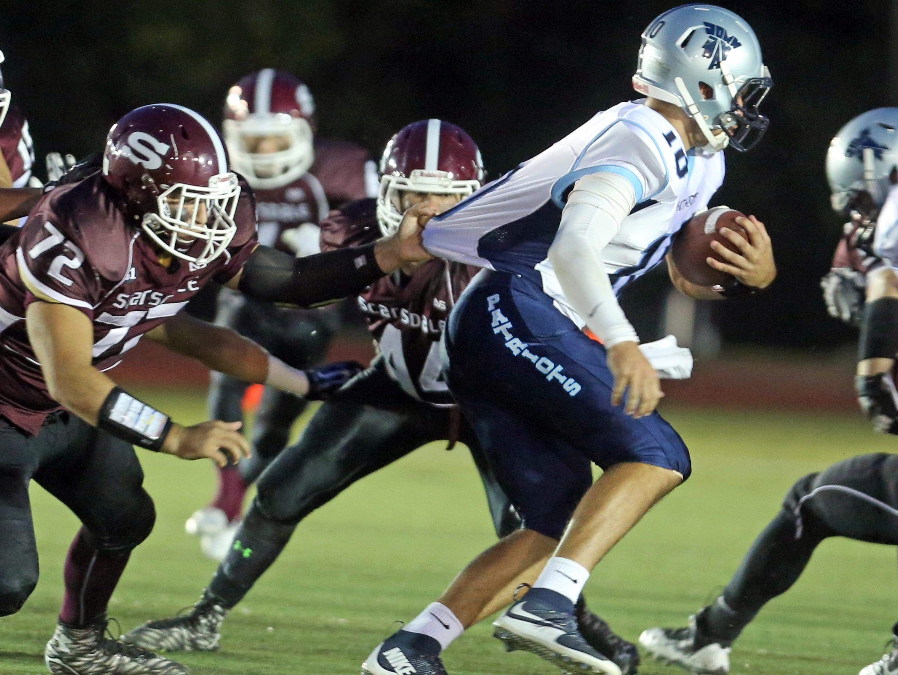 ]ohn Jay East Fishkill quarterback Ryan Schumacher is pulled down from behind by Scarsdale's Ethan Raff during a varsity football game at Scarsdale High School Sept. 25, 2015.