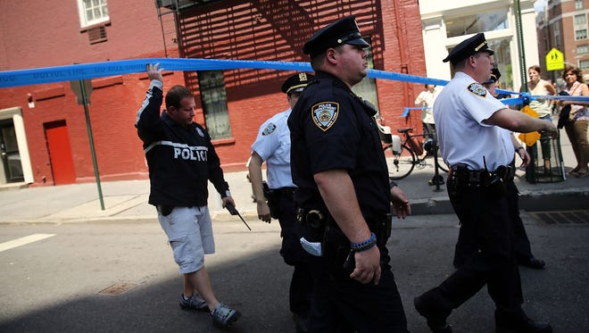 Police walk to where two U.S. Marshals and one New York Police Department detective were shot July 28 in the West Village of Manhattan, New York City.