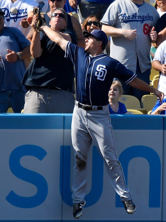 San Diego Padres left fielder Alex Dickerson collides with a fan as he tries to catch a ball hit for a two-run home run by Los Angeles Dodgers' Yasmani Grandal during the seventh inning of a baseball game, Sunday, Sept. 4, 2016, in Los Angeles. (AP Photo/Mark J. Terrill)