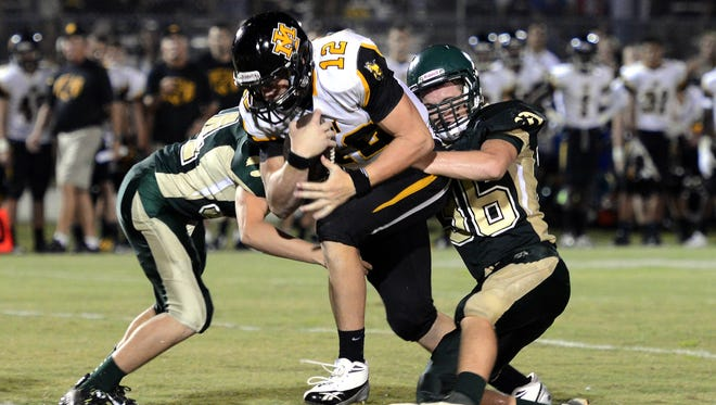 Merritt Island High quarterback Keegan Henderson is corralled by Viera players Brandon Mays (34) and Christian McDaniel (36) during the Kickoff Classic earlier this year.