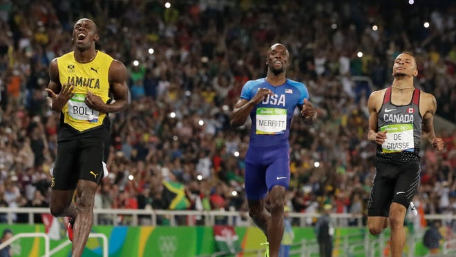 Usain Bolt from Jamaica, left, crosses the line to win the gold medal in the men's 200-meter final ahead of second placed Canada's Andre De Grasse, right, during the athletics competitions of the 2016 Summer Olympics at the Olympic stadium in Rio de Janeiro, Brazil, Thursday, Aug. 18, 2016.