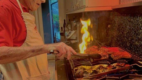 Peter Dupuis cooks ribs on the kitchen grill.