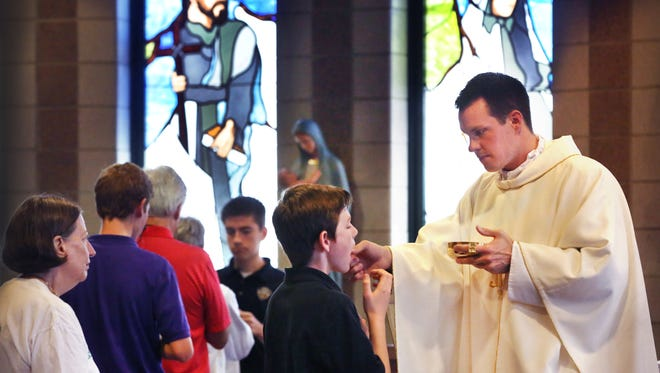 Father Thomas Haan, a priest at Guerin Catholic High School, 15300 Gray Rd., Noblesville, conducts mass in the school's chapel on Tuesday, September 29, 2015. A former football player, Haan, 29, passed his way into the state record books with 3,360 yards and 41 touchdowns as a senior at Lafayette Central Catholic High School. He was a walk-on freshman quarterback at Purdue during the 2005 season and spring 2006 before transferring to Notre Dame, where he completed his degree, but did not play football.