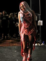 """In this Sept. 12, 2010 file photo, singer Lady Gaga walks backstage wearing a dress made of meat after accepting the award for video of the year for """"Bad Romance"""" at the MTV Video Music Awards in Los Angeles."""