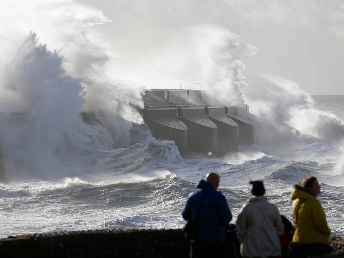 People watch as waves batter the sea wall at a marina in Oct. 28 in Brighton in southern England.