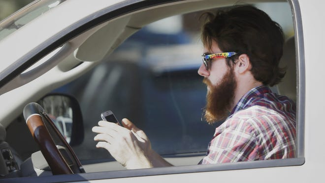 A man uses his phone while driving in 2013 in Dallas. Research from the Minnesota Department of Public Safety shows almost 30 percent of surveyed drivers operated vehicles while distracted.
