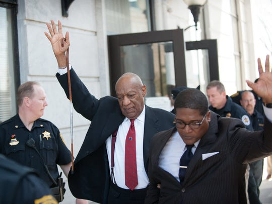 Bill Cosby gestures as he leaves the Montgomery County