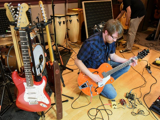 Dirty Mercury band member Brandon Surerus tunes his guitar and gets ready to record a guitar track for the band's next album Wednesday, April 27, at Rockhouse Productions in St. Joseph.
