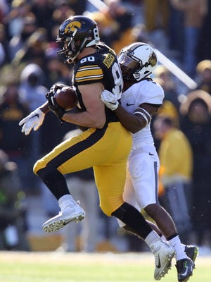 Iowa tight end Henry Krieger Coble catches a pass in front of Purdue safety Leroy Clark during the first half.