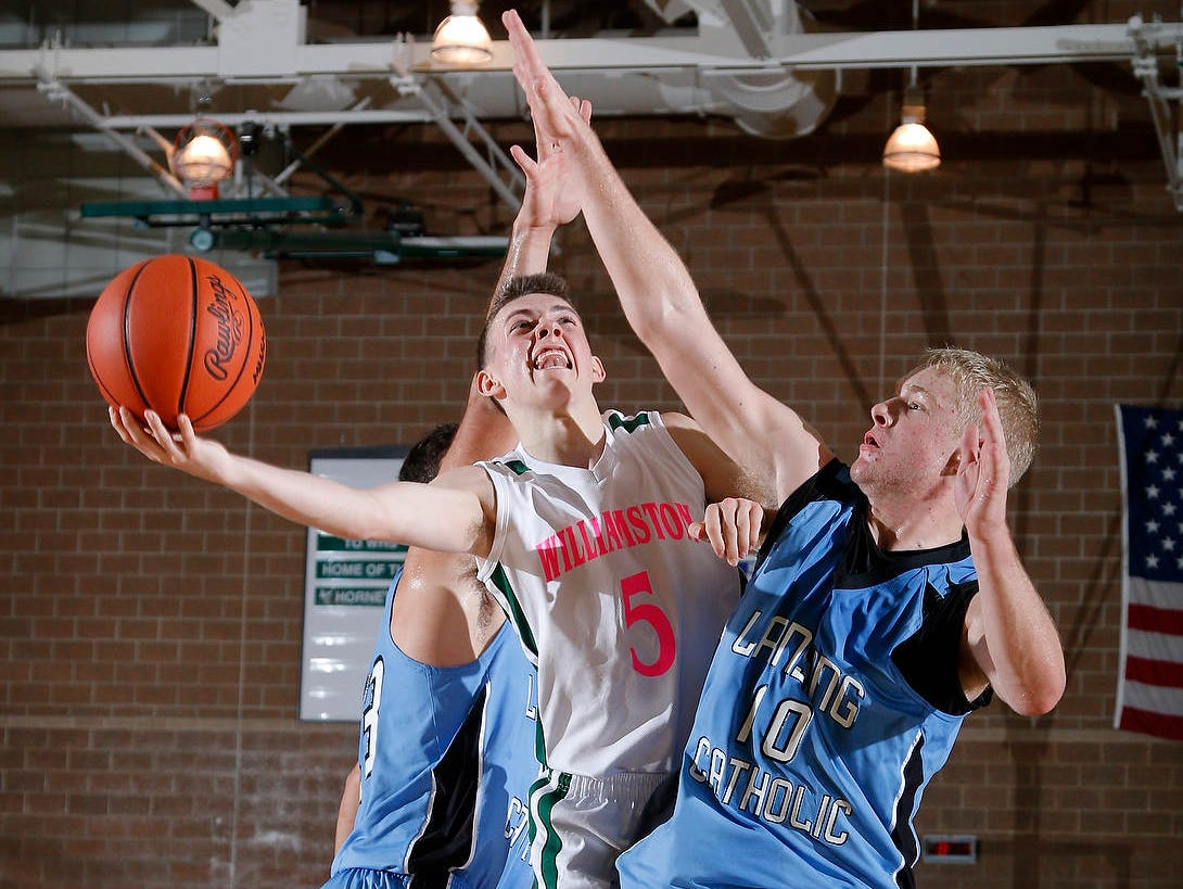 Williamston's Riley Lewis goes to the basket between Lansing Catholic's Connor Dartt, right, and Michael Korrey, left, during a contest in December.
