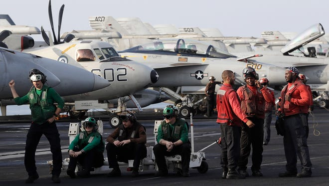 CORRECTS NAME OF SHIP - U.S. Navy sailors stand on the deck of the U.S.S. Dwight D. Eisenhower aircraft carrier on Tuesday, Nov. 22, 2016, U.S. Navy fighter jet takes off t. The carrier is currently deployed in the Persian Gulf, supporting Operation Inherent Resolve, the military operation against Islamic State extremists in Syria and Iraq. (AP Photo/Petr David Josek) ORG XMIT: PJO104