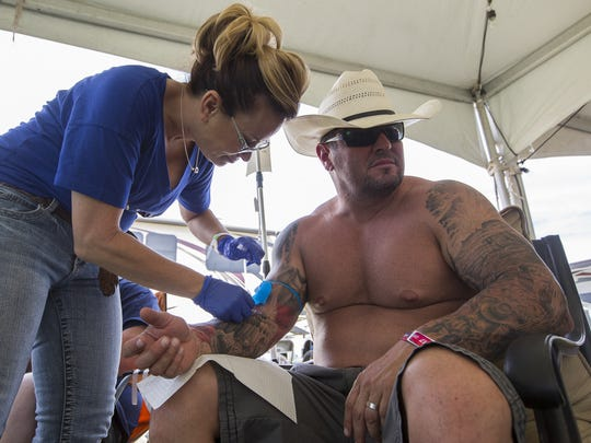 Donna Buoninontri (left) gives Joey Noriega (right) an IV drip so he can prep for the day at Country Thunder in Florence, Ariz. on Saturday, April 8th, 2017.