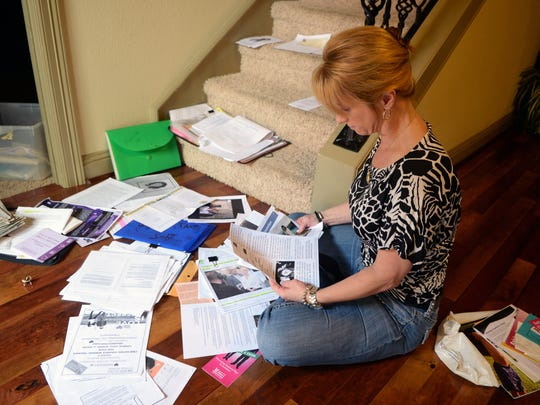 Theresa Donald surrounds herself with clippings documents of her sister's death at the hands of her husband in 2013. Donald's family received money from the crime victims reparation fund after her sister was murdered during a domestic violence crime.