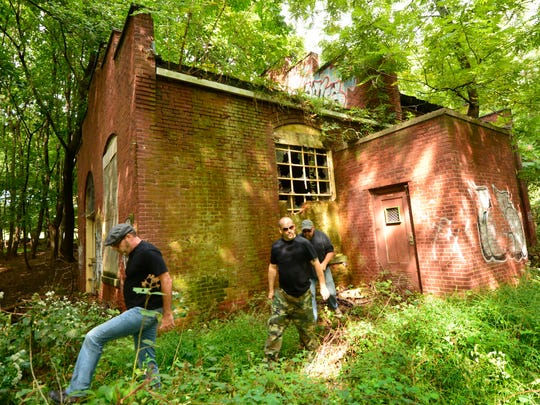 """Wheeler Antabanez, author of """"The Old Asylum and Other Stories,"""" center, and the editors of Weird NJ, Mark Sceurman, right and Mark Moran, exit their exploration of the remains of a pumphouse on the closed Overbrook Hospital Complex in Cedar Grove on Tuesday, Sept. 27."""