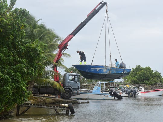 Men remove boats from the water ahead of Hurricane Maria in the Galbas area of Sainte-Anne on the French Caribbean island of Guadeloupe, early Monday, Sept. 18, 2017. Hurricane Maria grew into a Category 3 storm on Monday as it barreled toward a potentially devastating collision with islands in the eastern Caribbean.