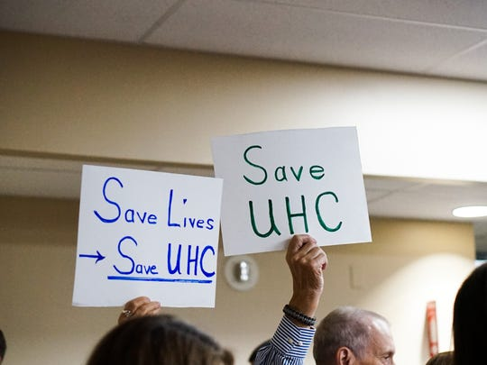 Signs call for state legislators to restore funding for University Hospital and Clinics, a charity medical system in Lafayette operated through a public-private partnership between the state and Lafayette General Health.