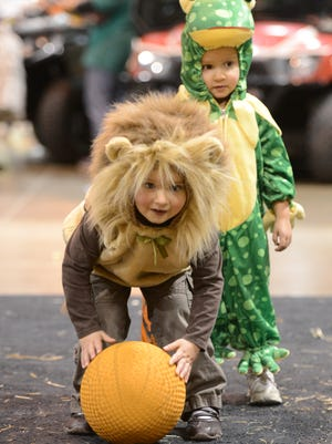 Madeline, left, and Ella Kessel of Green Bay try pumpkin bowling during Sweet Street at Shopko Hall on Friday.