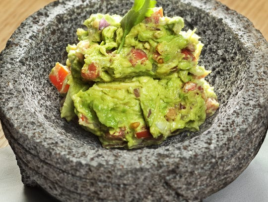 Guacamole made tableside is served in lava rock vessels