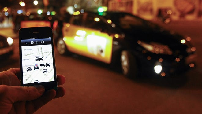 The Uber app is seen on a smartphone as cabs wait for clients in Barcelona.