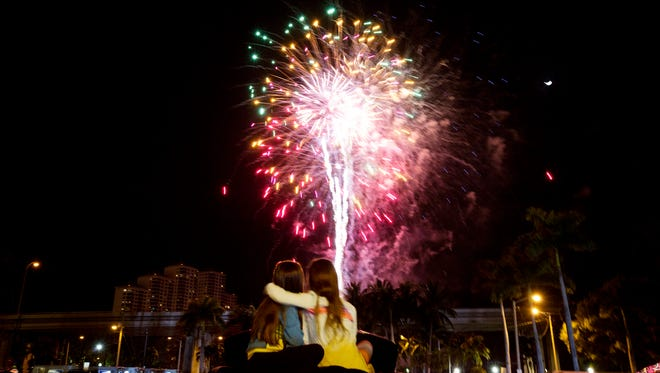 Savannah Martinez and Madison Darnell, both 7, enjoy the fireworks at the Edison Festival of Light Grand Parade on Saturday.