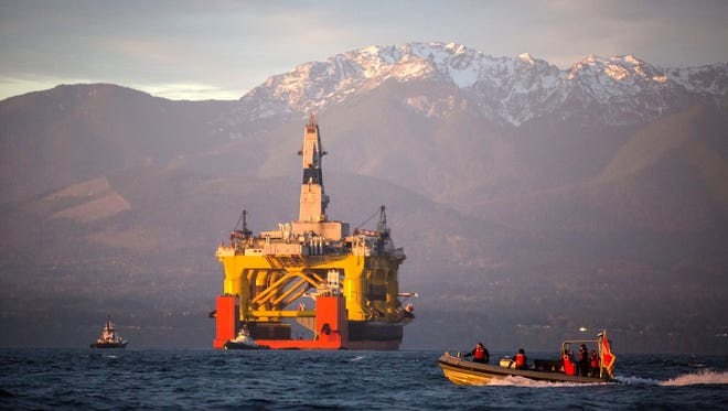 In this April 17, 2015 file photo, with the Olympic Mountains in the background, a small boat crosses in front of an oil drilling rig as it arrives in Port Angeles, Wash., aboard a transport ship after traveling across the Pacific.