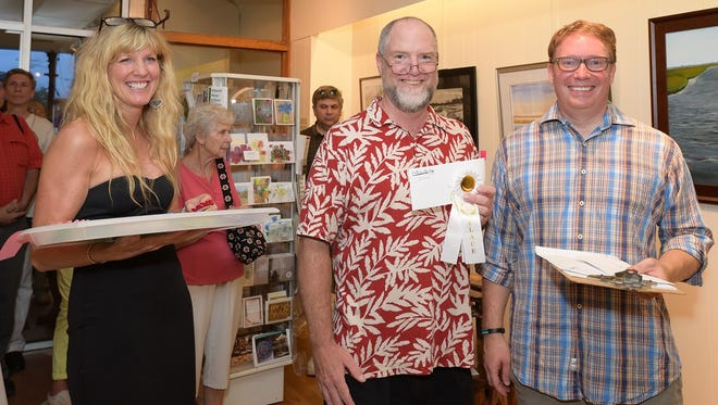 """Chuck Law (center) accepts the third place award for """"Greenwich Marina"""" from Matt Pisarski, director of the Cumberland County Cultural and Heritage Commission, and Sharon Kiefer, director of Gallery 50."""