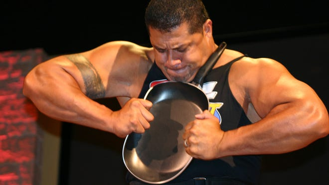 A Team Impact member folds a frying pan.