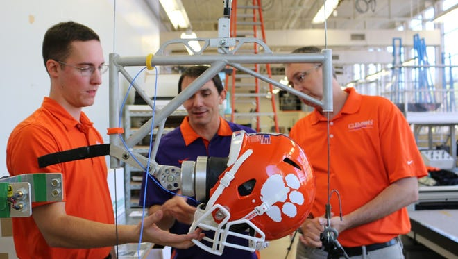 Alex Bina (left), Gregory Batt (center) and John Desjardins use a linear drop tower with an anthropomorphic head model for their football helmet facemask tests.