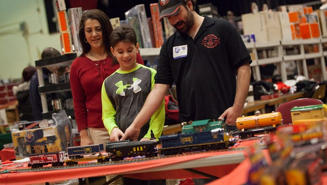 Joe Sanders of White Plains Trains and Hobbies shop in White Plains shows Gino Galante, 10 and Janine Galante, of Scarsdale, how to control the model trains at the annual Toy and Train Extravaganza at the Westchester County Center in White Plains, Jan. 29, 2017.