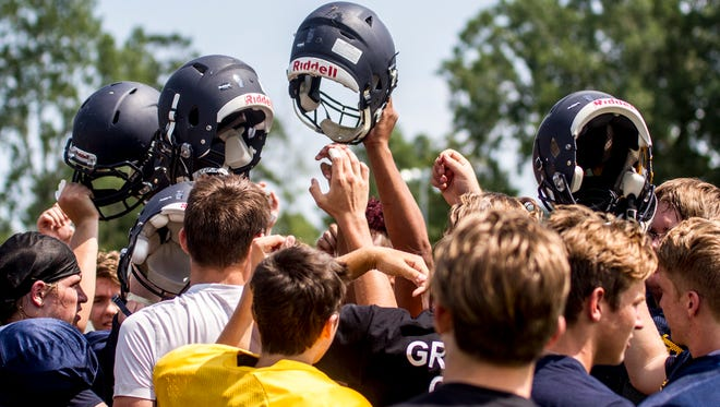 The Port Huron Northern Huskies hold their hands and helmets in the air for a cheer at the end of practice on Aug. 14. The Huskies' first game will be against Fraser at home at 7 p.m. Aug. 24.
