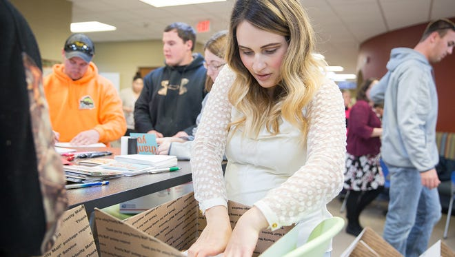 "Christine Gil fills a box with donations for military members during Moraine Park's ""Christmas in a Shoebox"" event held Wednesday in Beaver Dam."