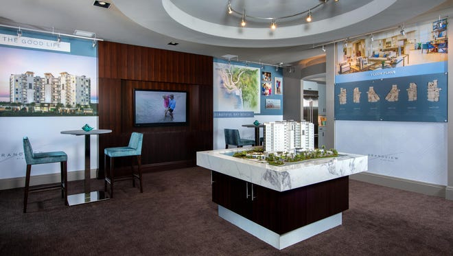 The Grandview at Bay Beach Sales Center features an 11-foot long arching wall of tempered-glass panels etched with the Grandview logo, a presentation theater, sales offices, a display area, and a full-size kitchen.